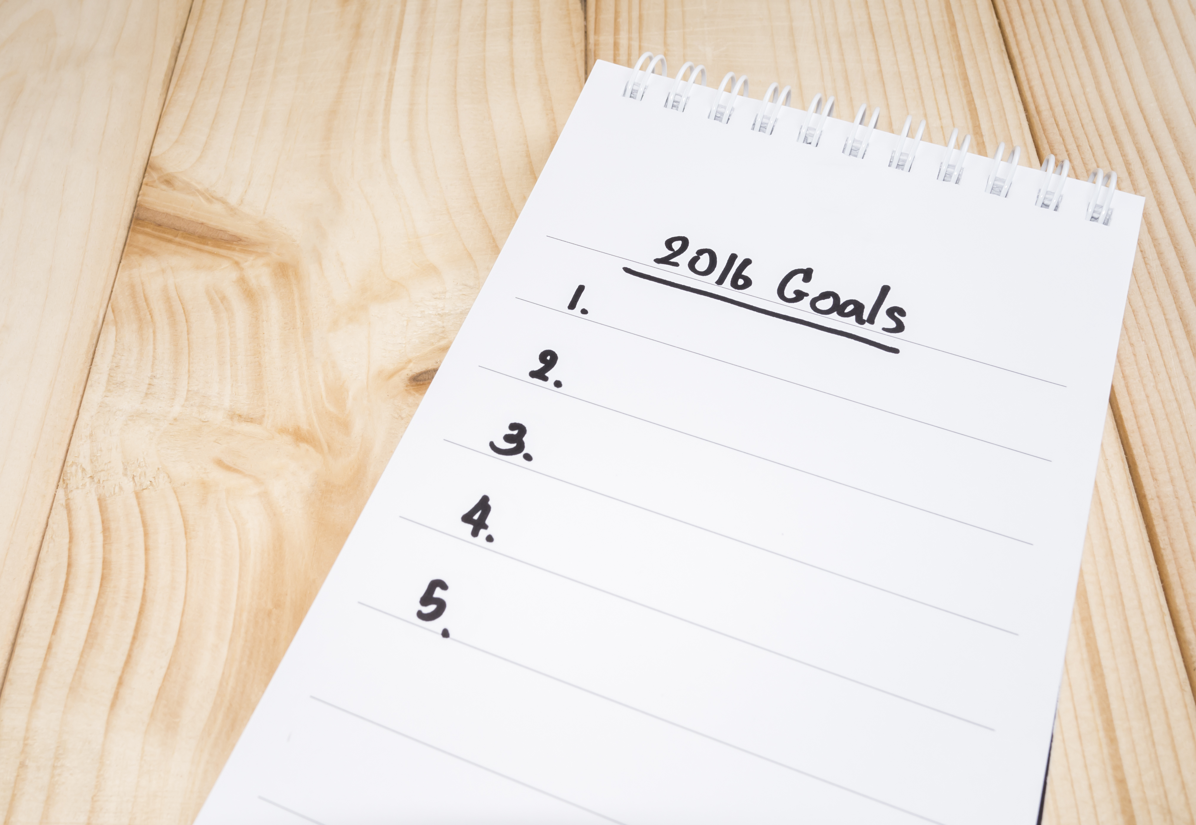 2016 Goals in notebook on wood background (Business Concept)